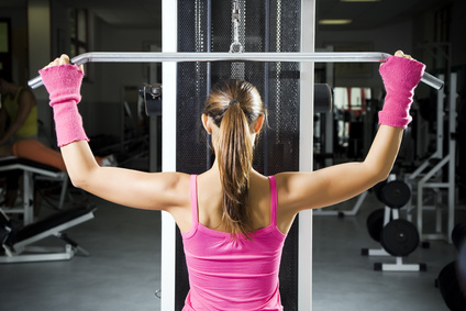 health club: girl in a gym doing weight lifting.